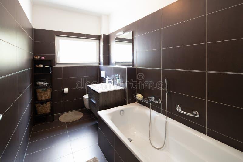 Современная ванная комната с коричневыми плитками и окном стоковые изображения rf