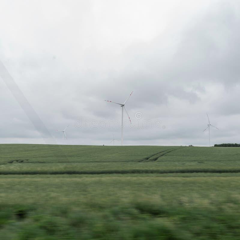 Современная ветрянка в зеленом поле на предпосылке пасмурное серое небо Экологичность и природа стоковое изображение rf
