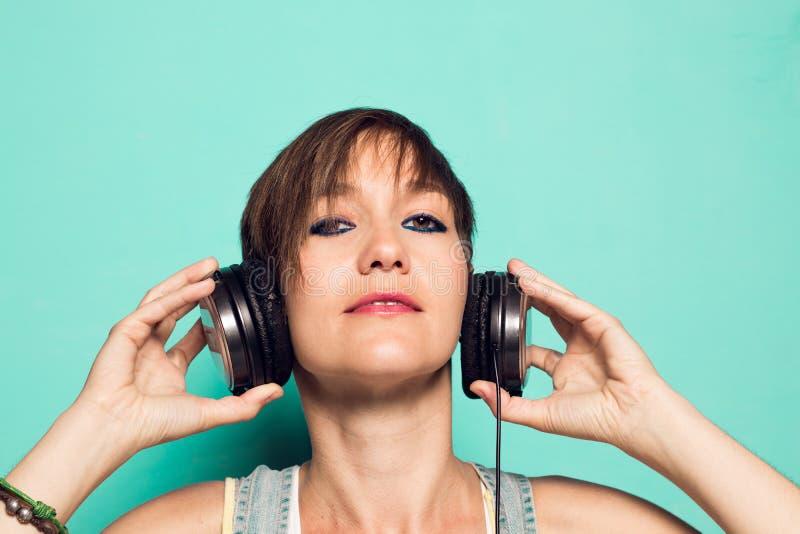 Современная девушка с наушниками музыки стоковые изображения