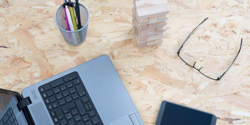 Современная деревянная таблица стола офиса с ноутбуком, стеклами смартфона и другим положением взгляда сверху поставок плоским стоковое изображение rf