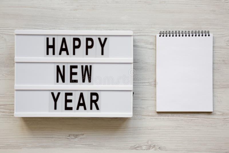 """Современная доска с текстом """"счастливым Новым Годом """"и пустым блокнотом над белой деревянной предпосылкой, взглядом сверху Надзем стоковое изображение rf"""