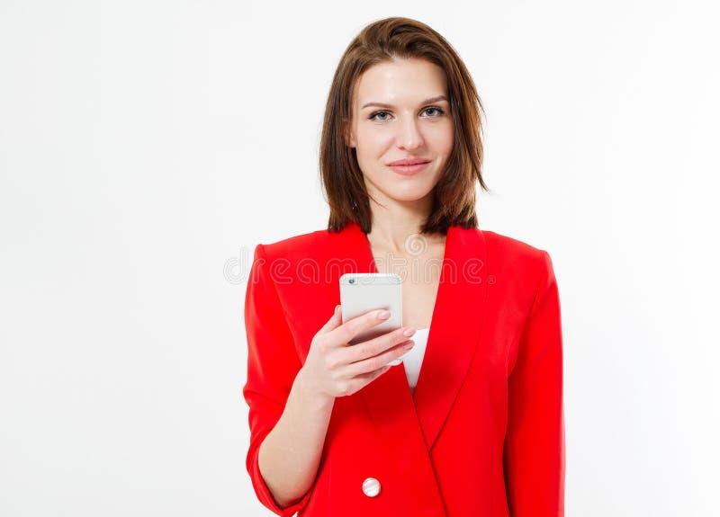 Современная женщина брюнета в красном сотовом телефоне владением костюма изолированном на белой предпосылке стоковая фотография rf