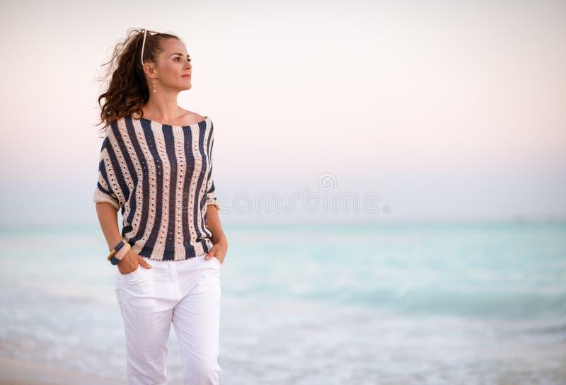 Современная женщина на береге моря в идти вечера стоковая фотография rf