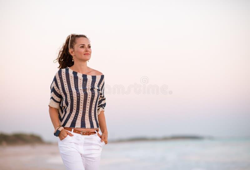 Современная женщина на береге моря на заходе солнца смотря в расстояние стоковые изображения rf