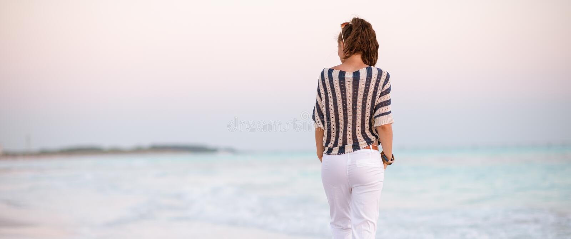 Современная женщина на seashore на идти захода солнца стоковые изображения rf