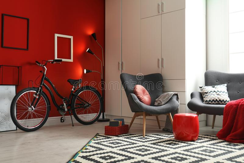 Современная живущая комната внутренняя с креслом, софой и велосипедом стоковое фото rf