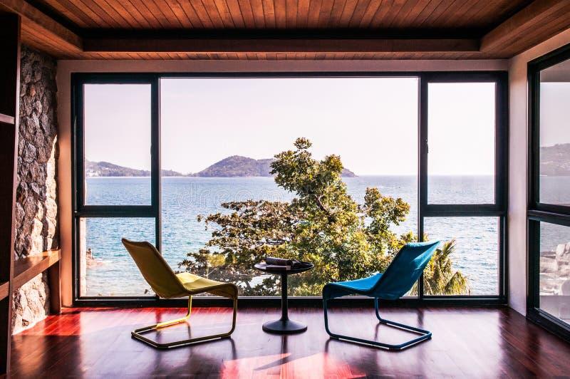 Современная живущая комната с красочным стулом с полом вида на океан к стоковые изображения