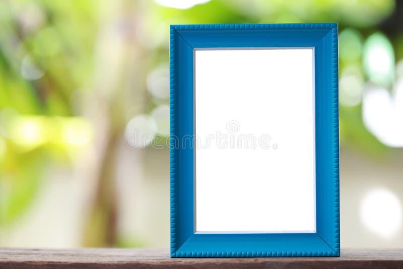 Современная картинная рамка помещенная на деревянном поле стоковые изображения rf