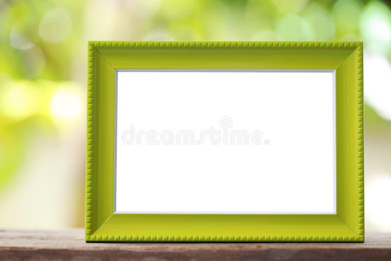 Современная картинная рамка помещенная на деревянном поле стоковое фото rf