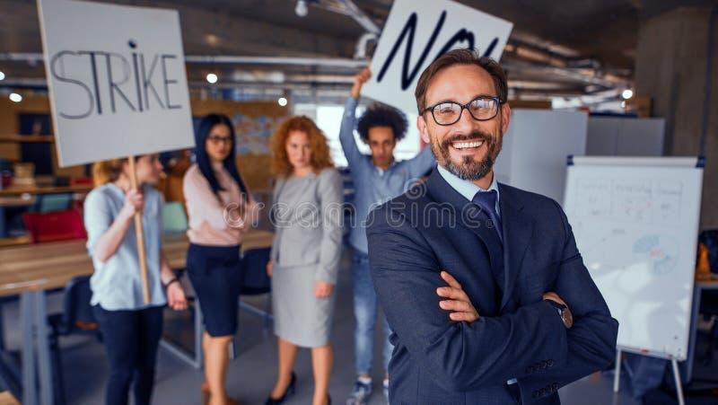 Современная концепция офиса, директор стоя с его задней частью к поразительным cowokers стоковое изображение