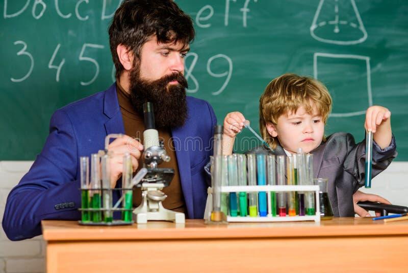 Современная лаборатория сын и отец в школе Биолог проводит эксперименты путем синтезировать смеси E стоковые фотографии rf