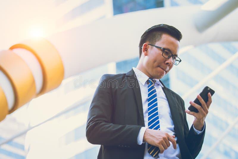 Современная молодая рука костюма черноты носки бизнесмена держа smartphone Офис профессионального бизнесмена стоящий внешний стоковая фотография