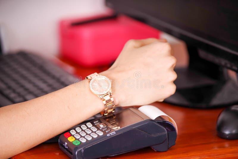 Современная оплата с новой технологией оплат используя умное обслуживание продуктов вахты, покупки и надувательства на деревянном стоковые изображения
