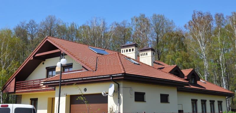 Современная панорама крыши дома с черепицами красной глины, окнами в крыше крыши и солнечными панелями нагревателей воды стоковое изображение