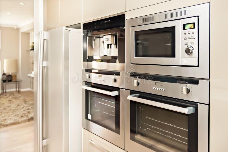 Современная печь и холодильник зафиксированные к стене с кладовкой стоковая фотография rf