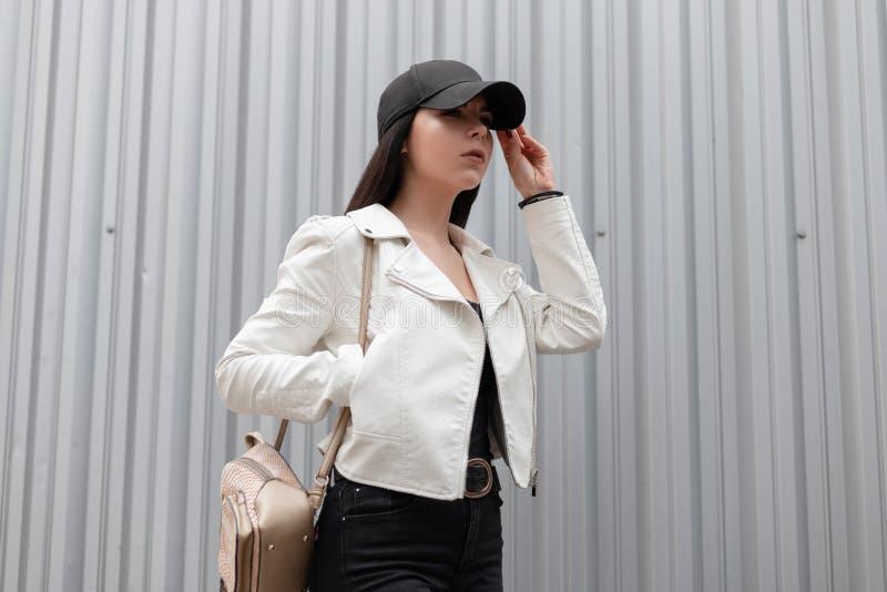 Современная привлекательная молодая женщина в стильной бейсбольной кепке в винтажной белой кожаной куртке в черных джинсах стоковые фото