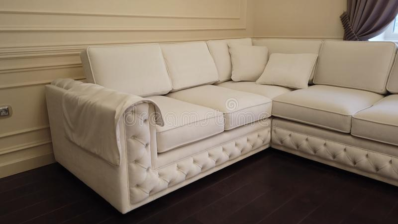 Современная роскошная живущая комната с белой кожаной угловой софой стоковое изображение