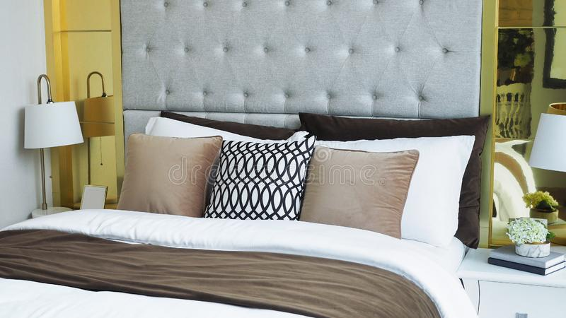 Современная спальня, подушки и подушки в белом, бежевом и коричневом тонах на кровати в роскошной спальне дома стоковые фото