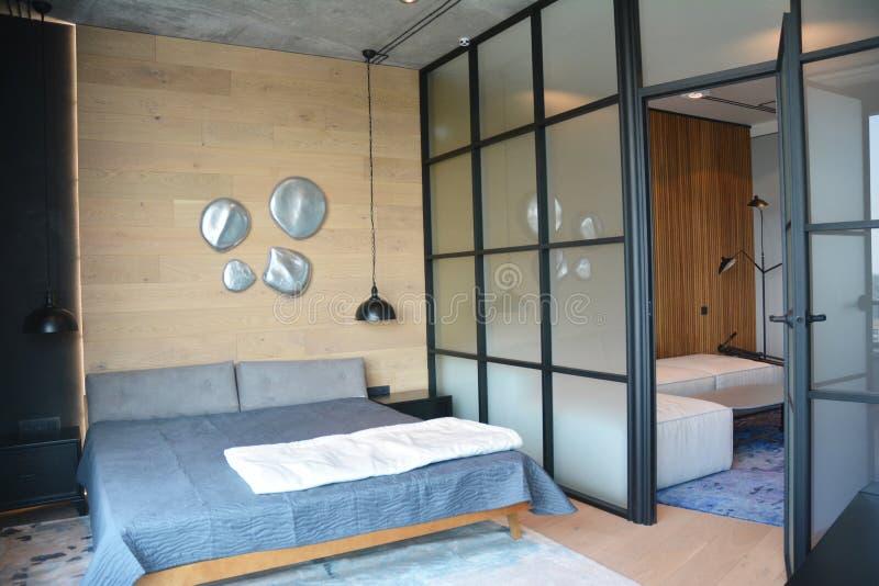 Современная спальня после реконструкции и реконструкции с современно оформленной стеклянной стеной и интерьером-лофтом стоковое фото