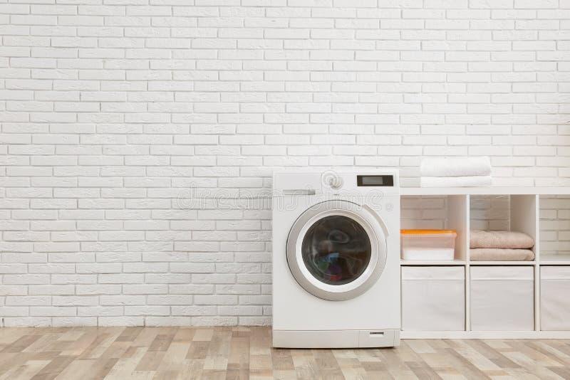 Современная стиральная машина около кирпичной стены в интерьере прачечной стоковое фото