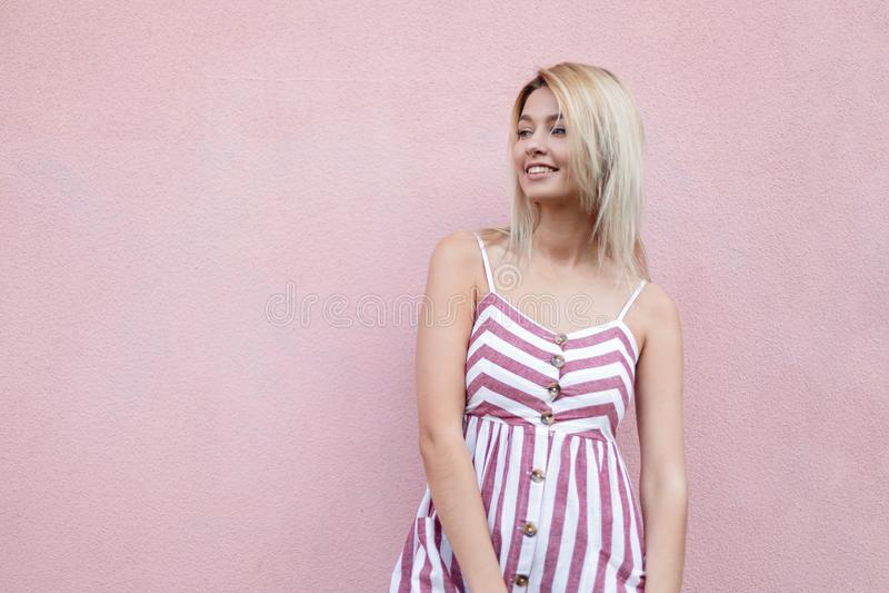 Современная счастливая стильная блондинка молодой женщины с милой улыбкой в ультрамодном striped платье представляя около розовой стоковое фото rf