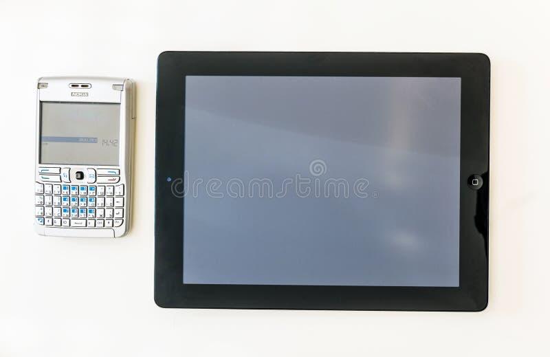 Современная таблетка и старый СТАНДАРТНО РАСПОЛОЖЕННЫЙ smartphone над финансовым временем стоковое изображение
