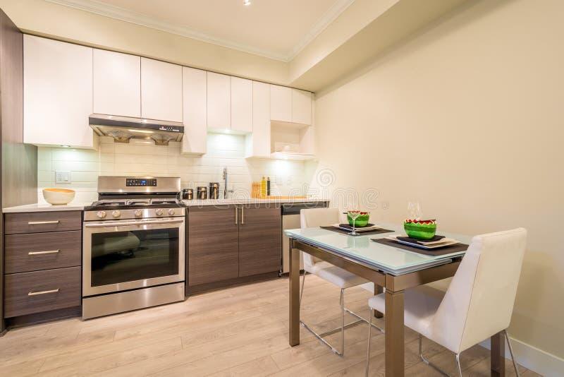 Современная таблица столовой установила для обедающего с кухней на заднем плане стоковые фото