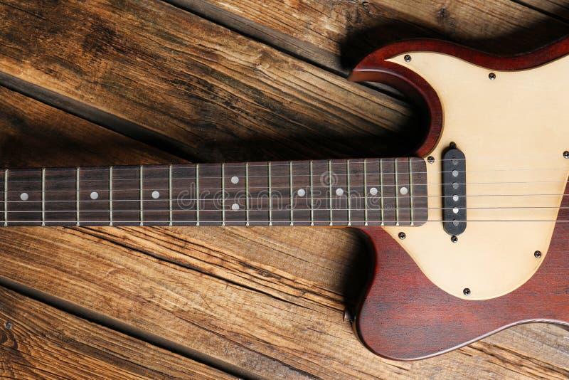 Современная электрическая гитара на деревянной предпосылке, взгляде сверху стоковое изображение
