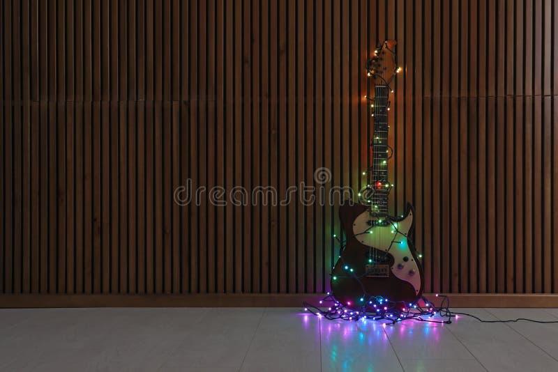 Современная электрическая гитара со светами рождества на поле около деревянной стены стоковые изображения