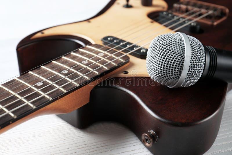 Современная электрическая гитара с микрофоном на деревянной предпосылке стоковые изображения rf