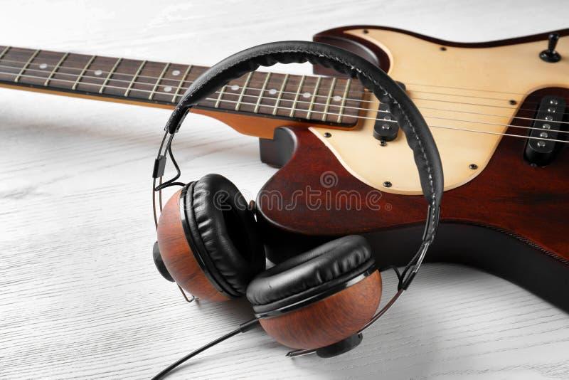Современная электрическая гитара с наушниками на деревянной предпосылке стоковая фотография rf