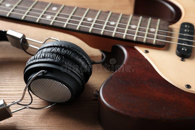 Современная электрическая гитара с наушниками на деревянной предпосылке стоковое изображение