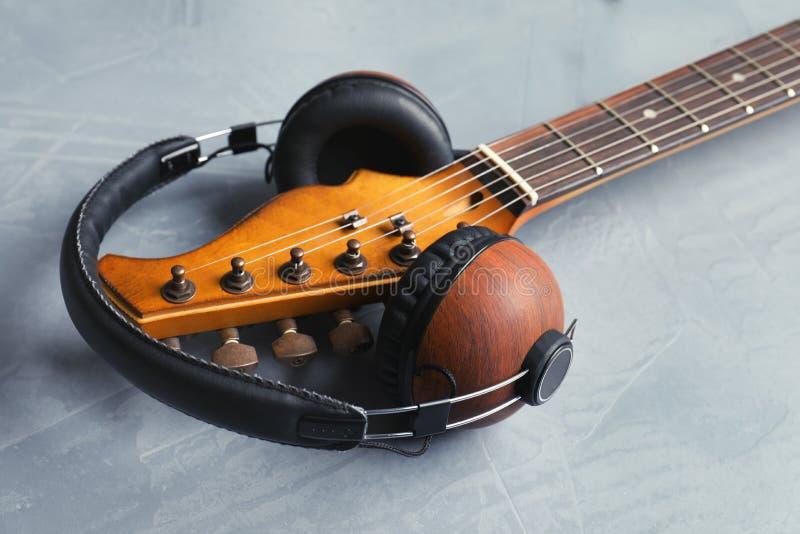 Современная электрическая гитара с наушниками на предпосылке цвета стоковая фотография
