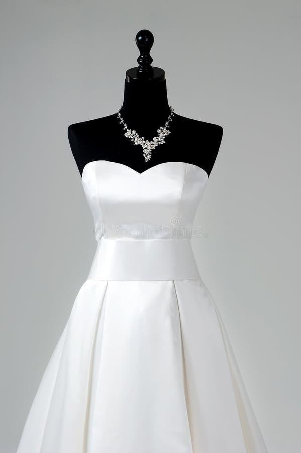 Современное белое платье свадьбы изолированное на серой предпосылке стоковое фото rf