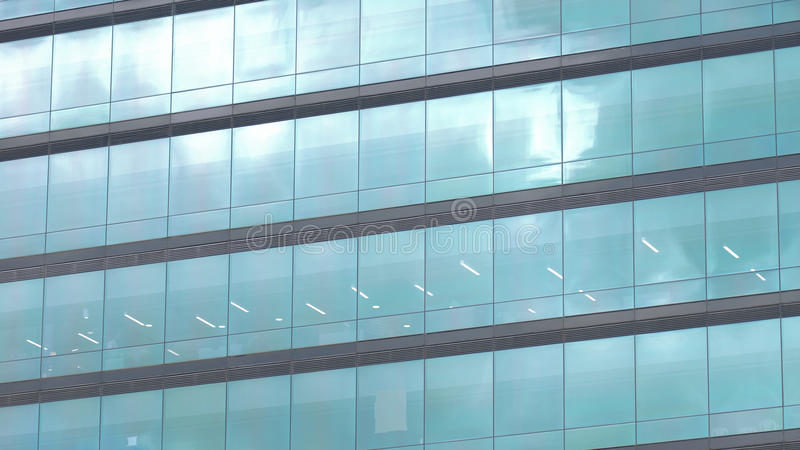 Современное здание с стеклянными окнами отразило небо стоковое фото