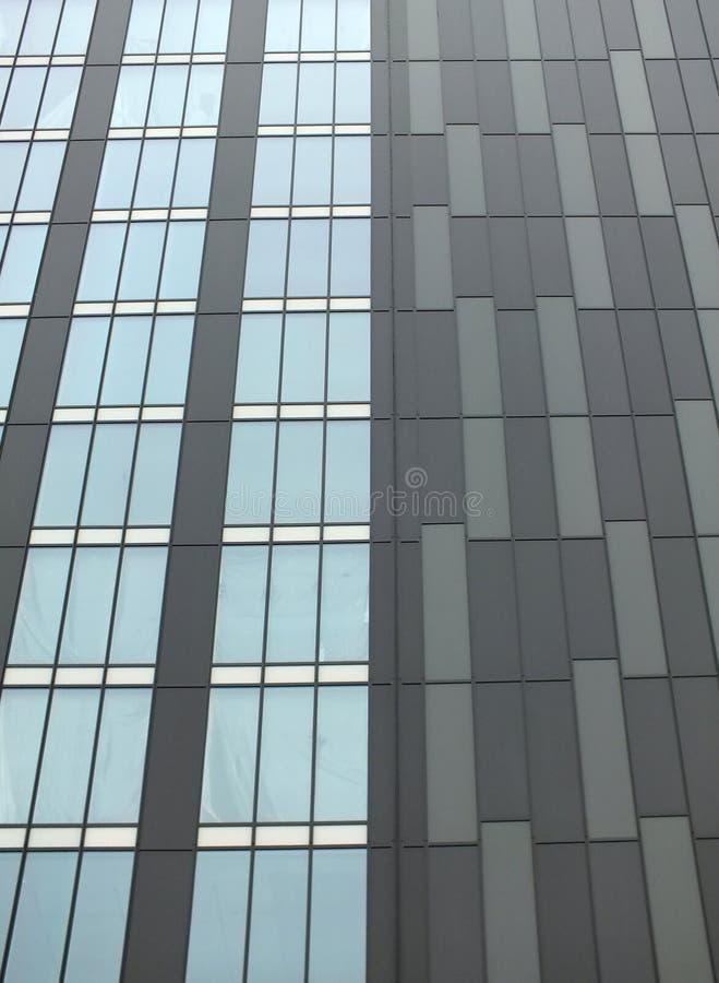 Современное здание highrise с серым плакированием и вертикальными окнами стоковая фотография