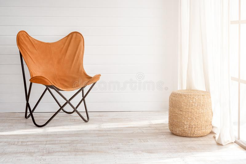 Современное кресло в современном интерьере просторной квартиры Солнечный день в светлой живущей комнате с панорамными окнами стоковое фото
