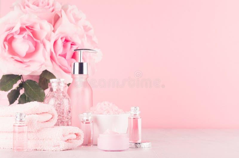Современное нежное girlish оформление bathroom - косметики для ванны и спа, букета роз, аксессуаров ванны на мягком белом деревян стоковая фотография rf