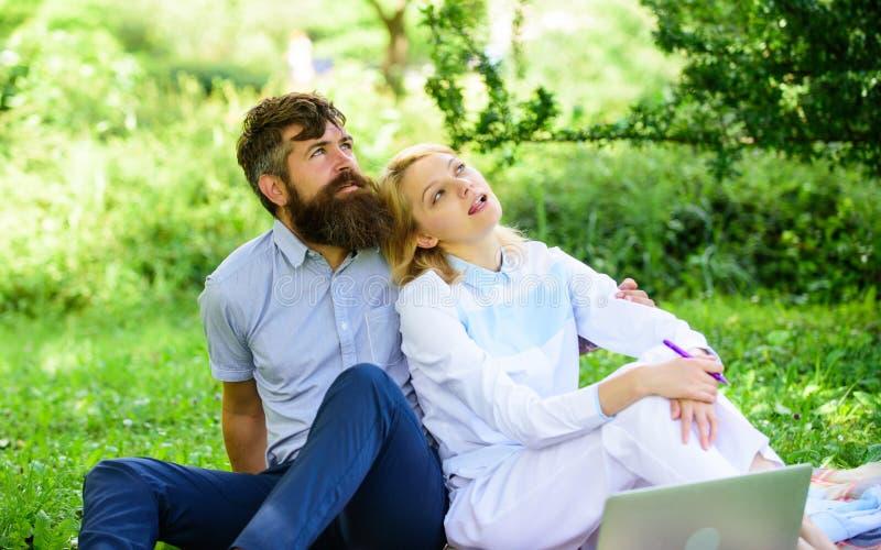 Современное онлайн дело Молодость пар тратит отдых outdoors работая с компьтер-книжкой Как сбалансировать независимое и семью стоковая фотография