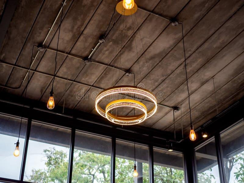 Современное потолочное освещение и электрические лампочки вися от деревянного потолка в здании стиля просторной квартиры стоковые фото