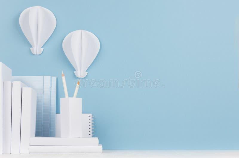 Современное рабочее место стиля - белые канцелярские принадлежности и декоративные бумажные воздушные шары на мягком голубом стол стоковое фото rf
