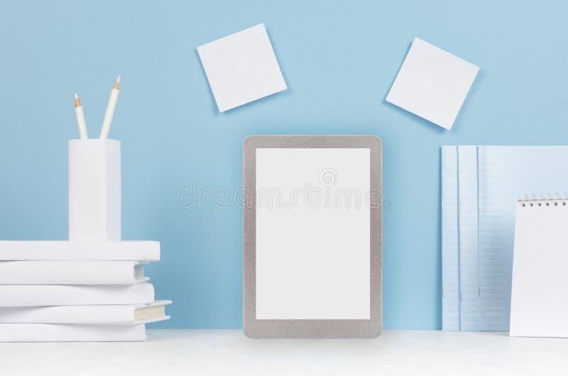 Современное рабочее место стиля - белые канцелярские принадлежности, пустой планшет на мягкой голубой предпосылке и стол света стоковые изображения