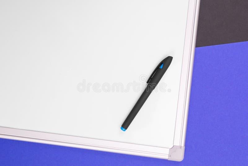 Современное рабочее место с тетрадью, ручкой и калькулятором изолированными на голубой черной предпосылке стоковая фотография