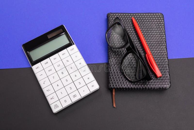 Современное рабочее место с тетрадью, ручкой и калькулятором изолированными на голубой черной предпосылке стоковое фото