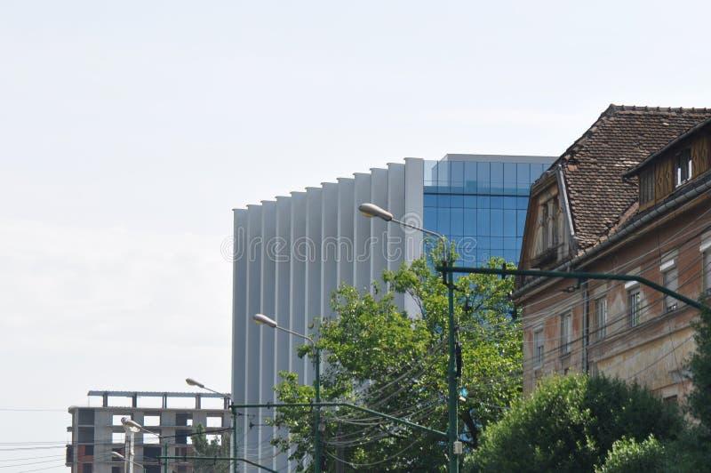 Современное стеклянное здание и ухудшенный дом стоковые фотографии rf