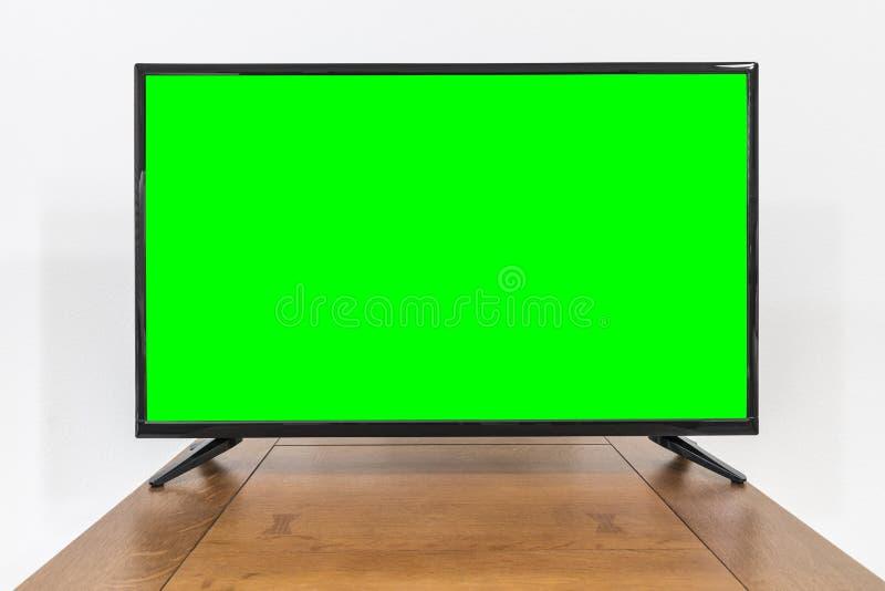 Современное телевидение на старой таблице с экраном Chroma ключевым зеленым стоковое фото rf