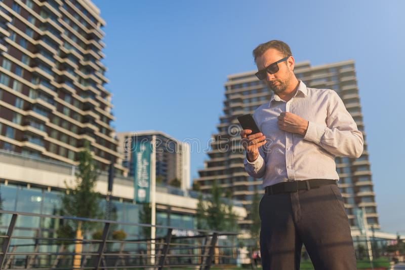 Современное удерживание предпринимателя и смотреть его мобильный телефон outdoors стоковые фото