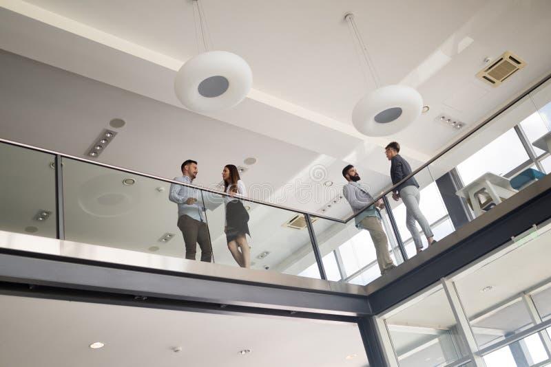 Современные бизнесмены идя на лестницы в стеклянной зале в офисе стоковая фотография rf