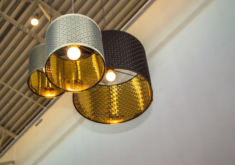 Современные декоративные лампы бронзы стиля и золотые абажуры висят на длинной веревочке, промышленном потолке, дизайне интерьера стоковые фото
