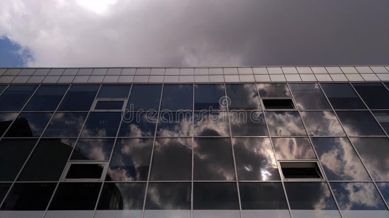 Современные детали здания в холодных цветах с отражением белых облаков стоковое фото